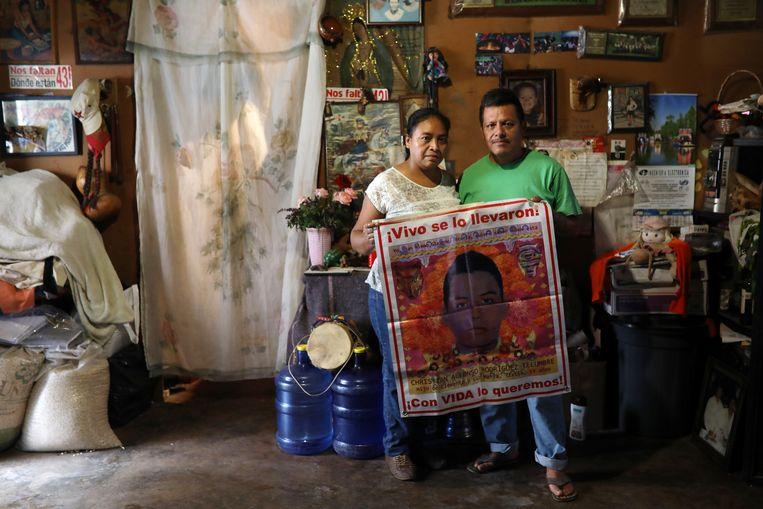 Luz Maria Telumbre en Clemente Rodriguez poseren met een doek met daarop een afbeelding van hun zoon Christian, een van de vele spoorloos verdwenen Mexicaanse studenten. Beeld -
