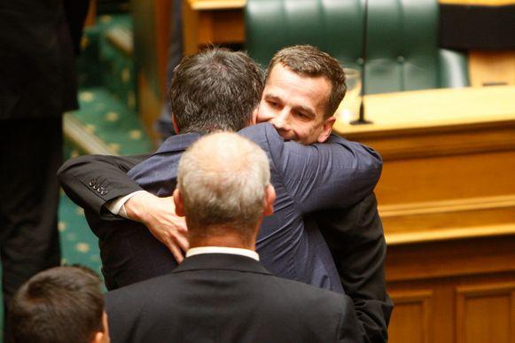 David Seymour, voorvechter van de euthanasiewet in Nieuw-Zeeland, wordt na de stemming omhelsd in het parlement.