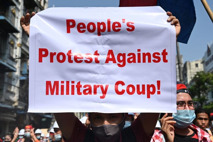 TOPSHOT - A protester holds up a sign during a demonstration against the military coup in Yangon on February 6, 2021. (Photo by YE AUNG THU / AFP)