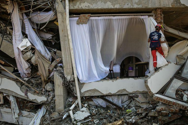 Een Frans lid van de internationale noodbrandweer gaat in het zwaar toegetakelde Mercure Hotel op zoek naar slachtoffers. Beeld AFP