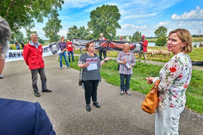 Minister Cora van Nieuwenhuizen wordt, onderweg naar de ondertekening van een bestuursakkoord voor de dijkversterking, aangesproken door de SP in verband met de stort van granuliet in de Maas bij Lith.