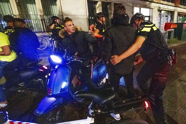 Politieagenten controleren in augustus 2020 jongens in de Schilderswijk in Den Haag, als het er voor de derde nacht op rij onrustig is.  Beeld ANP