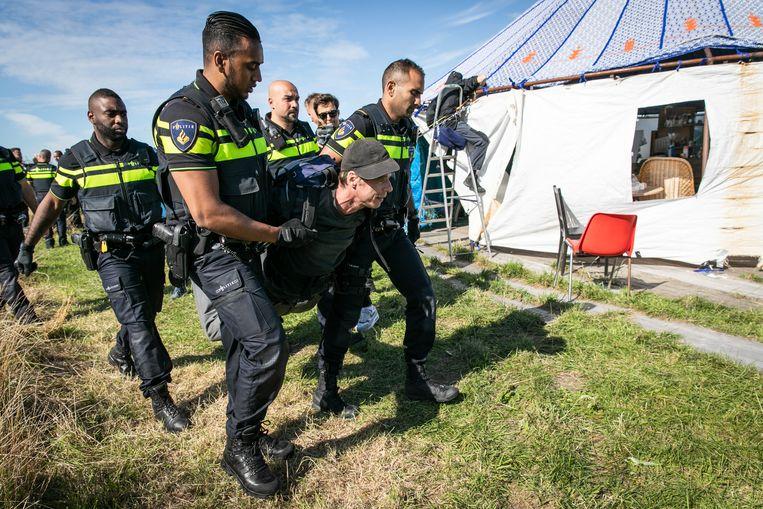 Een actievoerder wordt opgepakt en het terrein afgedragen. Het bezette stuk land in de Lutkemeerpolder is ontruimd door de politie. De actievoerders boden lang weerstand. Niet iedereen verliet vrijwillig het terrein. Beeld Dingena Mol