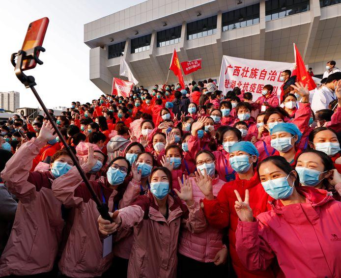 Verplegend personeel in Wuhan  lacht achter het masker: zestien tijdelijke ziekenhuizen zijn weer gesloten. In de stad is de situatie anderhalve maand na de quarantaine onder controle.