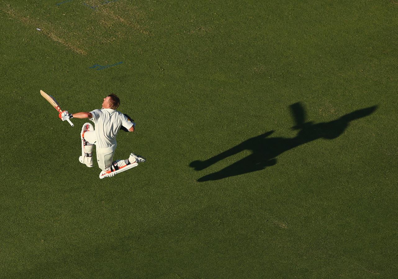 David Warner, een cricketer uit Australië springt een gat in de lucht na een score.