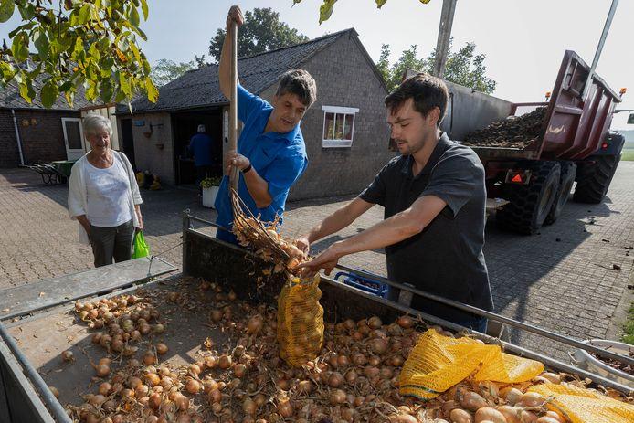 Charlie Engelen (midden) schept voor een klant uien in een zak.    midden *Charlie Engelen*