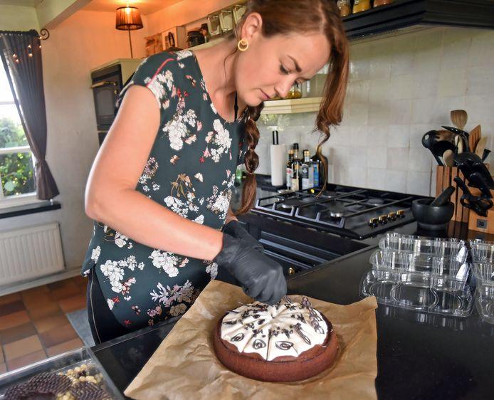 Anke Willeme legt de laatste hand aan een cappuccinocake met roomkaastopping.