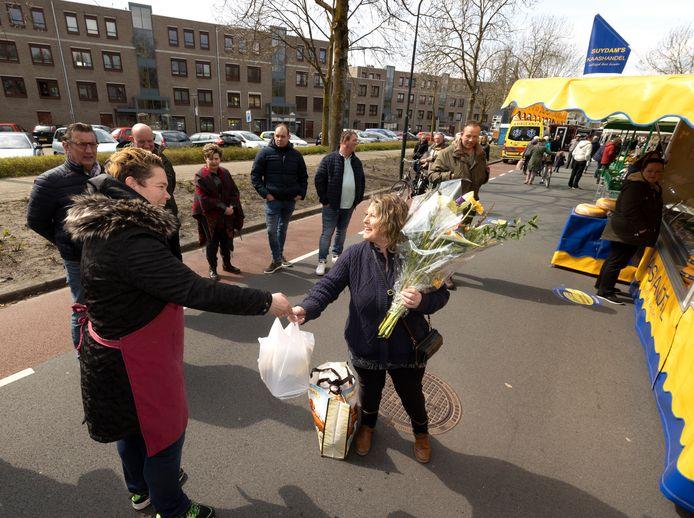 Kaasboerin Mirella van Suijdam overhandigt tassen met levensmiddelen aan marktkooplui die niet op de markt mogen staan.