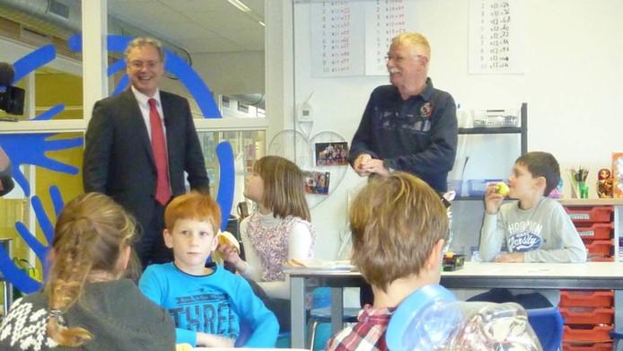 Een verraste Kees van Vugt (rechts) kreeg donderdagochtend op basisschool de Wijde Wereld in Uden bloemen van wethouder Gerrit Overmans. De klas was minstens zo verbaasd.