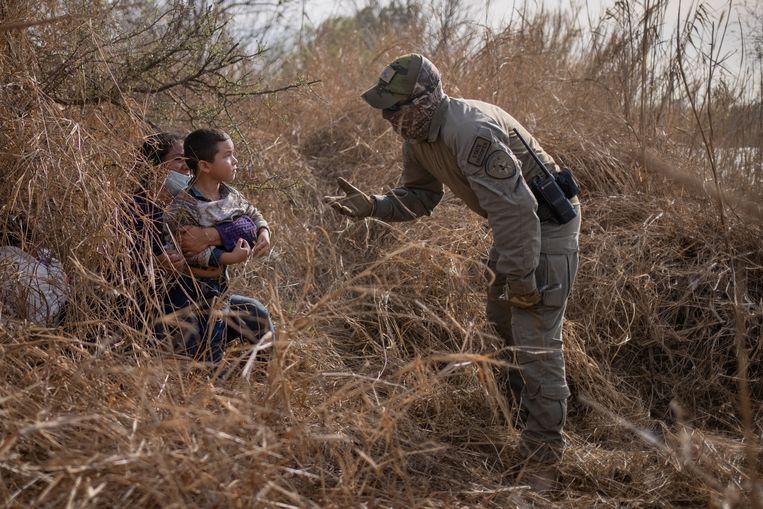Een agent van de Texaanse grenspolitie bij Hondurese asielzoekers die zich in het struikgewas verschuilen nadat ze begin deze maand met een vlot de Rio Grande Rivier zijn overgestoken.  Beeld Reuters
