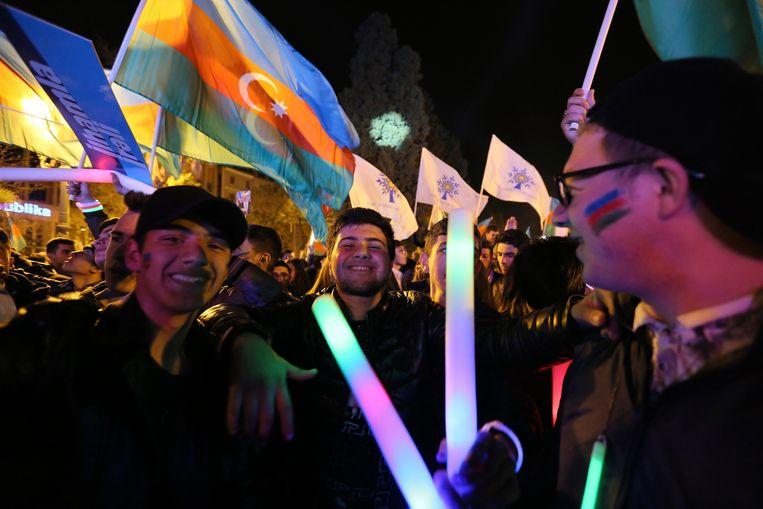 Aanhangers van president Ilham Aliyev in Azerbeidzjan nadat bekend geworden heeft dat hij de verkiezingen heeft gewonnen. Beeld AP