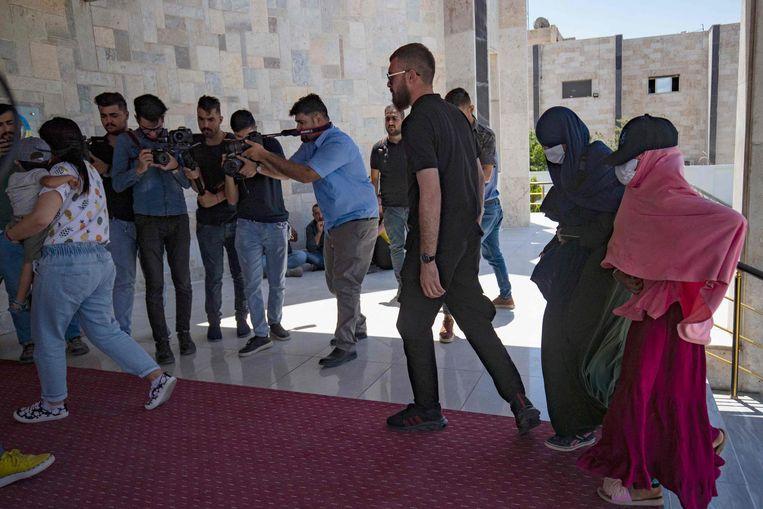 Leden van de Koerdische veiligheidsdienst begeleiden IS-ganger Ilham B. en haar familie, voordat ze aan Nederlandse diplomaten worden overgedragen.   Beeld AFP