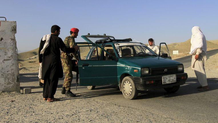 Afghaanse soldaten doorzoeken een voertuig. Beeld REUTERS