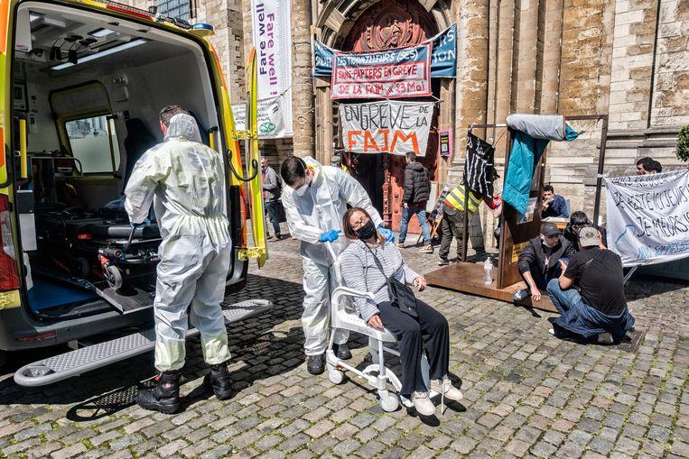 Hulpverleners brengen een verzwakte dame naar de ambulance.   Beeld Tim Dirven