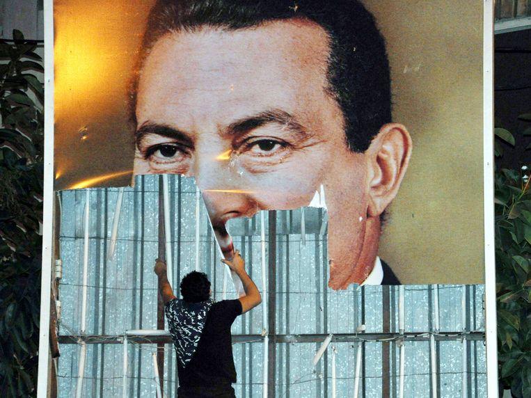 25 januari 2011: een demonstrant in de Egyptische stad Alexandrië verwijdert een poster van de toenmalige president Moebarak. De volksopstand tien jaar geleden leidde tot diens val. Beeld EPA