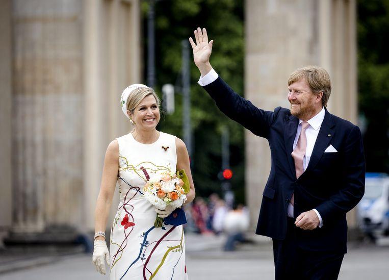 Koning Willem-Alexander en koningin Maxima zwaaien naar publiek bij de Brandenburger Tor. Beeld ANP