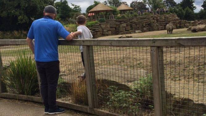 Vader laat zoontje tussen de neushoorns poseren in dierentuin