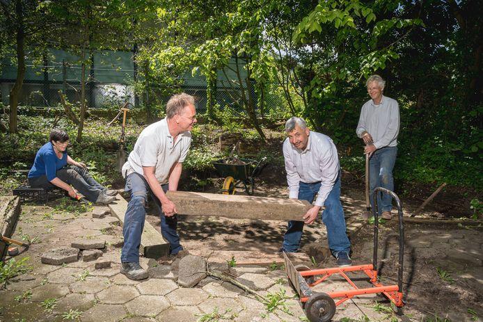 Vrijwilligers knappen de tuin op van Uniplastic.