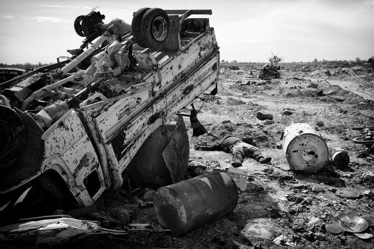 Een gedode IS strijder ligt tussen de puinhopen van Baghuz. Beeld Eddy van Wessel