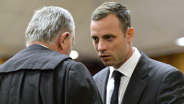 Oscar Pistorius in gesprek met zijn advocaat bij aanvang van de rechtszaak Beeld ap