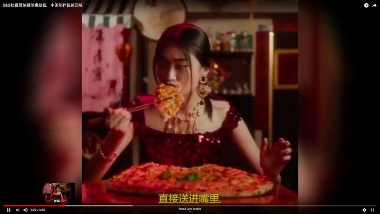 Een stilstaand beeld uit de bewuste video van Dolce & Gabbana, waarin een Aziatische vrouw probeert om een pizza op te eten met stokjes. De video is ondertussen offline gehaald.