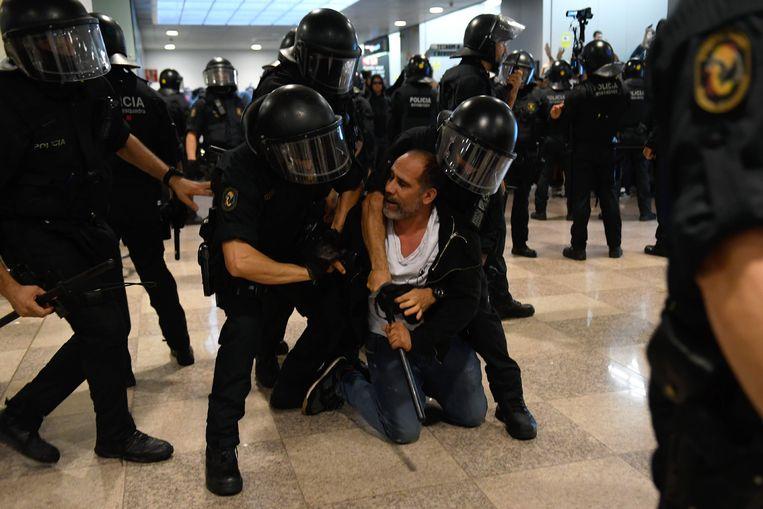 De politie arresteert een betoger in de luchthaven El Prat. Beeld AFP