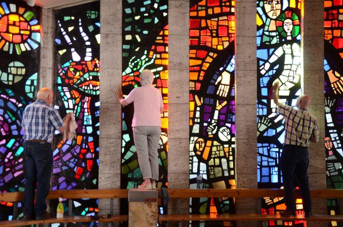 Vrijwilligers Karel Bergmans en Bea en Jan Simons (vlnr) poetsen glas-in-betonraam van de kapel van OLV ter Nood in Tilburg