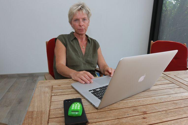 Anita Martel achter de laptop. Op de voorgrond haar digipass. Ze werd het slachtoffer van phishing.