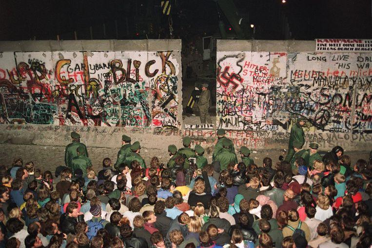 Oost-Duitse grenswachten slopen een sectie van de Berlijnse Muur, waardoor een nieuwe doorgang tussen Oost en West ontstaat. Berlijn, 12 november 1989. Beeld AFP