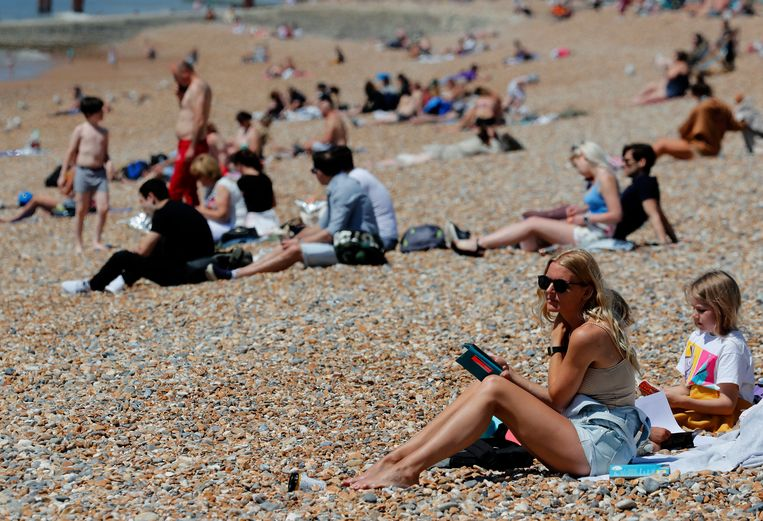 Mensen genieten van het warme weer op het strand van het Engelse Brighton. Beeld AP