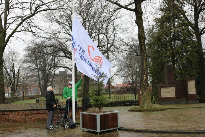 Oud-verzetsstrijder Roelf Wolterink en Johan Nijeboer hijsen de vlag van het herdenkingscomité bij het Rijssens oorlogsmonument.
