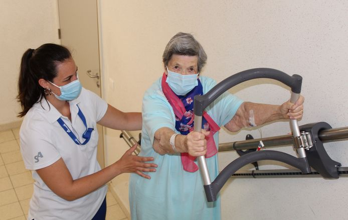 Kinesiste Justine helpt een patiënte met de traplift