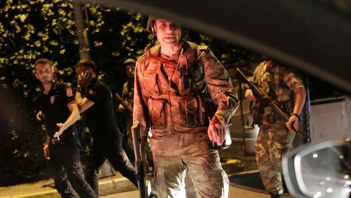 Militairen met geweer te zien vanuit een auto.