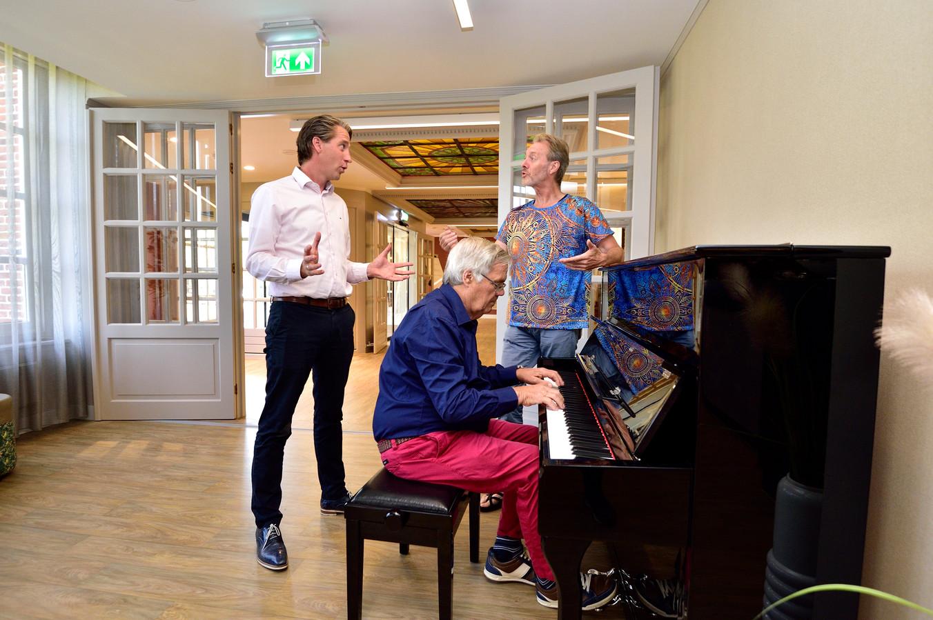 Bewoner Herbert IJsseldijk van het Amadeushuis speelt 'De Zilvervloot' op de piano. Directeur Eric van der Linde en de Goudse muzikant Henny Brink (rechts) zingen met hem mee.