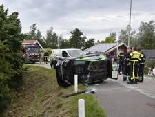 Automobiliste knalt op geparkeerde auto; auto op zijn zijkant en een rolt de dijk af