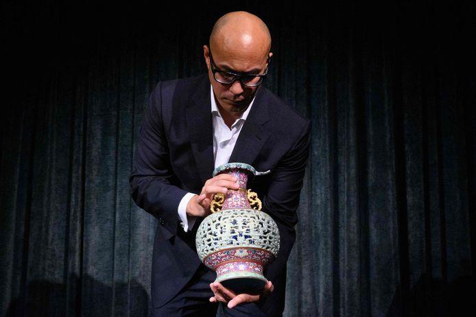 Nicolas Chow, voorzitter van Sotheby's Asia met de Chinese vaas in handen.