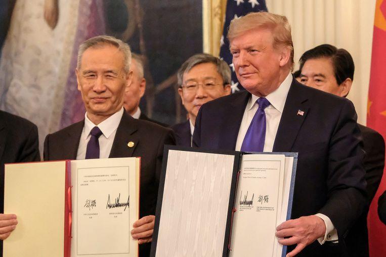 De Amerikaanse president Donald Trump en de Chinese vicepremier Liu He poseren nadat ze een handelsakkoord hebben ondertekend in het Witte Huis in Washington, op 15 januari 2020.  Beeld EPA