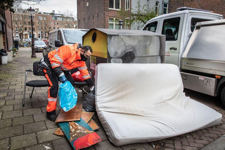 Een melding van vuilnis op straat naast een glasbak  in de Eerste Marnixdwarsstraat. Beeld Dingena Mol
