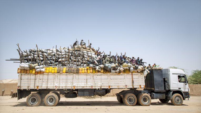 Een vrachtwagen vertrekt vanuit Agadez, de hoofdstad van Niger, naar Dirkou, de laatste stop voor Libië. Vanuit Libië hopen de migranten de oversteek naar Europa te maken. Beeld Sven Torfinn