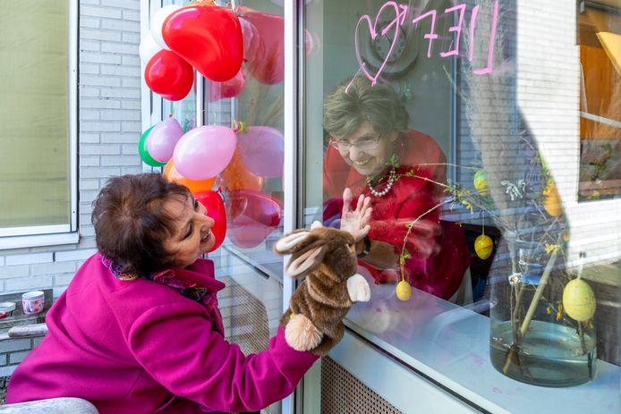 Louise Nagtegaal bezoekt haar dementerende moeder Ulrike (102) die achter het raam in woonzorgcentrum Snavelenburg in Maarssen op haar zit te wachten vanwege de coronacrisis.