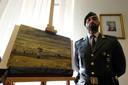 Een Italiaanse politieman naast een van de teruggevonden schilderijen.