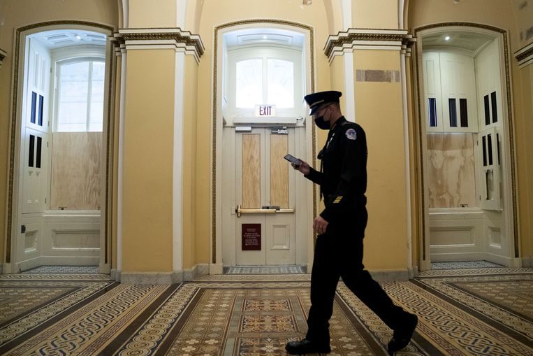 Een agent van het politiekorps van het Capitool loopt een gang waarvan de kapotgeslagen ramen met houten planken provisorisch zijn dichtgemaakt. Beeld AFP
