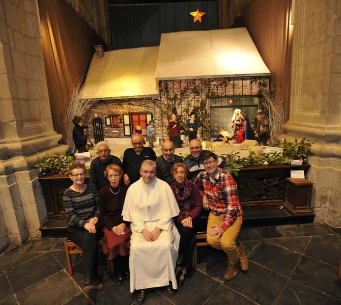 Pastoor Johan Goossens met de groep vrijwilligers voor de kerststal.