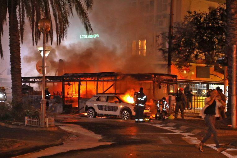 Bij de raketaanval op Tel Aviv door Hamas gingen ook auto's in vlammen op. Beeld AFP