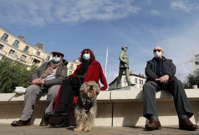 Mensen met gezichtsmaskers zitten bij een lokale markt in Nice, Frankrijk.  Beeld REUTERS