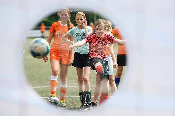 Goed mikken en scoren maar! De bal in een gat schieten is een van de onderdelen van het Oranjefestival voor meisjes.