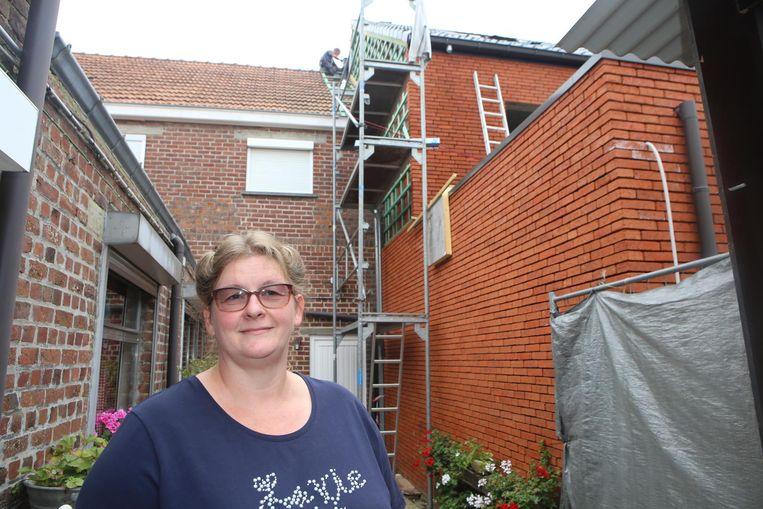 Marleen Braeken bij de stellingen en de bewuste muur van de buren op haar eigendom. Ook de houten latjes waaraan de leien zullen bevestigd worden, hangen er al.