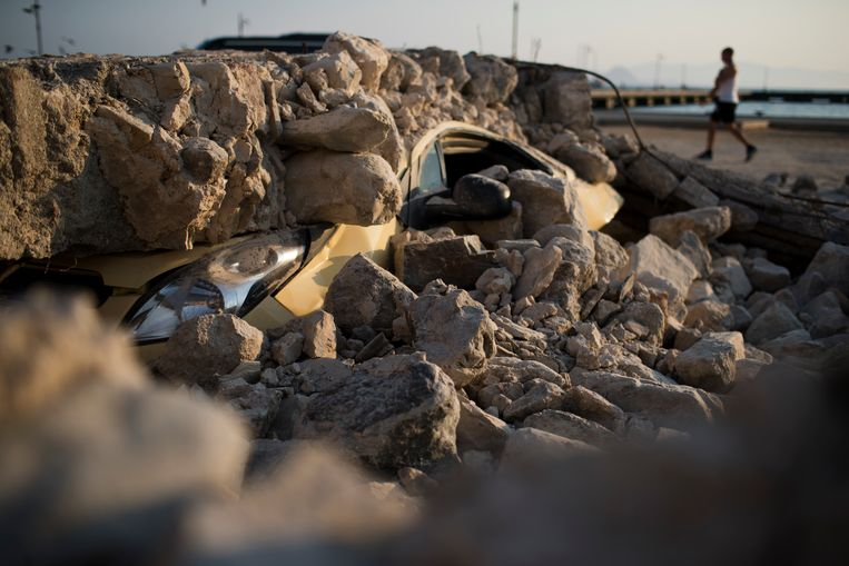 A man walks past a car crushed under rubble near the port of the Greek island of Kos on Saturday, July 22, 2017. Hundreds of residents and tourists on the eastern Greek island of Kos spent the night sleeping outdoors, on beach lounge-chairs, in parks and olive groves or in their cars, a night after a powerful earthquake killed two tourists and injured nearly 500 others across the Aegean Sea region, in Greece and Turkey. (AP Photo/Petros Giannakouris) Beeld AP