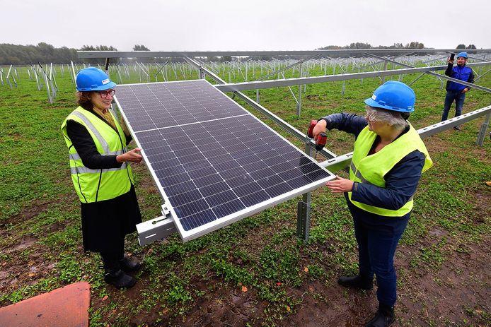 Marlies Bartels (links) van Stichting Energietransitie Roosendaal en wethouder Klaar Koenraad leggen het eerste panneel van zonnepark Weihoek.