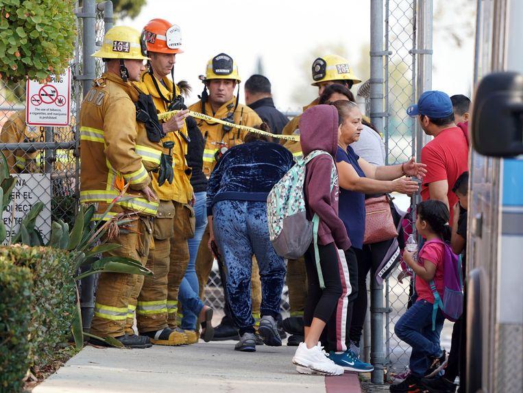De brandweer laat ouders binnen in Park Avenue Elementary School waar meerdere kinderen en volwassenen werden behandeld na blootstelling aan kerosine. Beeld AP